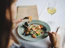一件美丽的礼服的一个女孩在一家美丽的餐馆吃着一个可口海鲜盘 完善的时间,鲜美食物 库存图片