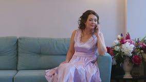 一件美丽的礼服的一个女孩谈话在电话,当坐长沙发时 股票视频