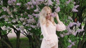 一件美丽的礼服的一怀孕的年轻女人在公园走 一件桃红色礼服的一名怀孕的白肤金发的妇女在站立 股票录像