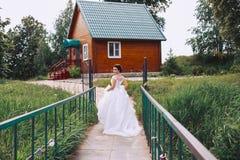 一件美丽的礼服的新娘沿桥梁走 库存照片
