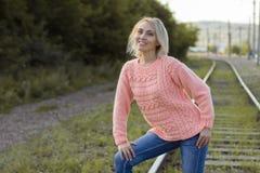 一件美丽的被编织的夹克的孤独的妇女 步行的美丽的妇女 蓝色衣裳时兴的查出的人s毛线衣白色 37企业夫人 专属handicr 免版税库存照片