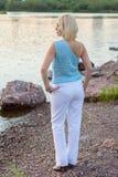 一件美丽的被编织的夹克的孤独的妇女 步行的美丽的妇女 蓝色衣裳时兴的查出的人s毛线衣白色 37企业夫人 专属handicr 免版税库存图片