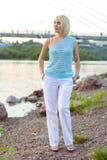 一件美丽的被编织的夹克的孤独的妇女 步行的美丽的妇女 蓝色衣裳时兴的查出的人s毛线衣白色 37企业夫人 专属handicr 免版税图库摄影