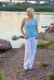 一件美丽的被编织的夹克的孤独的妇女 步行的美丽的妇女 蓝色衣裳时兴的查出的人s毛线衣白色 37企业夫人 专属handicr 库存图片