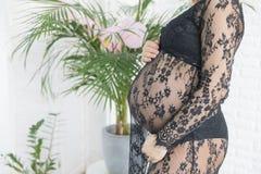 一件美丽的鞋带礼服的孕妇握腹部 库存照片