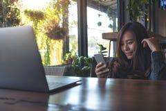 一件美好的亚洲女商人藏品的特写镜头图象,使用和看有膝上型计算机的巧妙的电话在木桌上 图库摄影