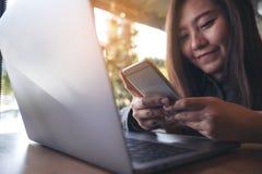 一件美好的亚洲女商人藏品的特写镜头图象,使用和看有膝上型计算机的巧妙的电话在木桌上 免版税库存照片