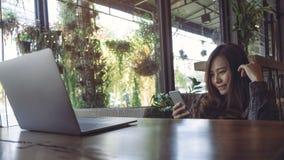 一件美好的亚洲女商人藏品的特写镜头图象,使用和看有膝上型计算机的巧妙的电话在木桌上 免版税库存图片