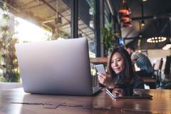一件美好的亚洲女商人藏品,使用和看有膝上型计算机和片剂个人计算机的巧妙的电话的特写镜头图象在木t 免版税库存图片