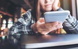 一件美好的亚洲妇女藏品的特写镜头图象,使用和看充满感觉的巧妙的电话放松和膝上型计算机 免版税库存照片
