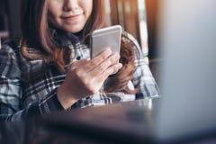 一件美好的亚洲妇女藏品的特写镜头图象,使用和看有膝上型计算机的巧妙的电话在桌上 免版税库存图片
