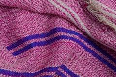 一件老羊毛披肩的红色蓝色织品纹理 库存图片