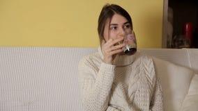 一件舒适温暖的毛线衣的一个女孩在家平衡饮用的茶和考虑某事的一个冬天 股票视频