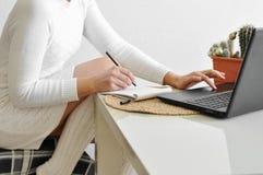 一件舒适白色毛线衣和袜子的一个主妇女孩在与毯子的一把椅子与一台膝上型计算机一起使用在厨房里 网上购物的w 库存图片