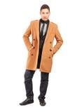 一件英俊的微笑的人佩带的外套的全长纵向 库存图片