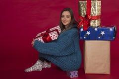 一件蓝色毛线衣的女孩在礼物旁边坐 免版税库存照片