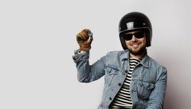 一件蓝色牛仔布夹克的假装年轻的骑自行车的人骑被隔绝的摩托车在白色背景 举行手moto的人 免版税库存照片