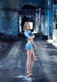 一件蓝色牛仔布夹克立场的一个美丽的长腿的女孩在一家被毁坏的商店的曲拱的背景 图库摄影