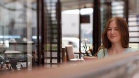 一件蓝色礼服的一个女孩从在咖啡馆的一张桌起来 女孩微笑着 影视素材