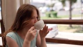 一件蓝色礼服的一个女孩喝在夏天咖啡馆的咖啡 影视素材
