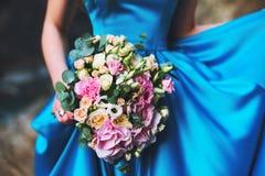 一件蓝色礼服的一个女孩拿着花婚礼花束从玫瑰的 免版税库存照片