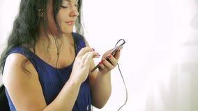 一件蓝色礼服的一个少妇听到在她的电话的音乐 特写镜头 股票视频