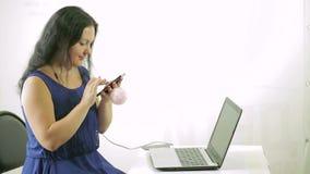 一件蓝色礼服的一个少妇在她的电话写着一则消息 股票视频