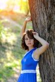 一件蓝色礼服的一个年轻深色的女孩在一棵大树附近摆在明亮的太阳的光芒的一个夏天公园 库存照片