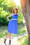 一件蓝色礼服的一个年轻深色的女孩在一棵大树附近摆在明亮的太阳的光芒的一个夏天公园 免版税库存图片