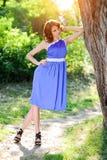 一件蓝色礼服的一个年轻深色的女孩在一棵大树附近摆在明亮的太阳的光芒的一个夏天公园 免版税库存照片