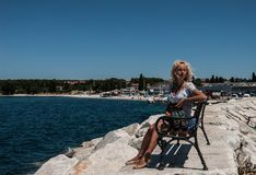 一件蓝色礼服的一名年轻白肤金发的妇女坐长凳在海附近并且看对边 免版税库存图片