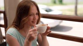 一件蓝色礼服的女孩喝在咖啡馆的咖啡 影视素材