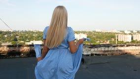 一件蓝色礼服的女孩有无所事事在屋顶的圆点的 影视素材