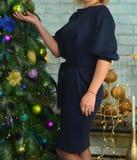 一件蓝色礼服的妇女有在她的胳膊的一条红色螺纹的,在圣诞树附近的立场,拿着一个玩具 库存图片