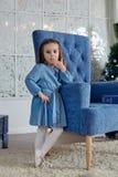 一件蓝色礼服的小女孩在一把蓝色椅子附近站立 免版税库存图片