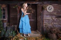 一件蓝色礼服的美丽的金发碧眼的女人 免版税库存图片