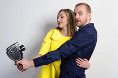 一件蓝色衬衣和一个年轻亭亭玉立的女孩的人有老电影摄影机的一件黄色礼服的 库存图片
