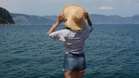 一件蓝色衬衣和牛仔布短裤的女孩支持草帽的海 股票录像