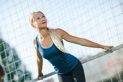 一件蓝色衬衣和绑腿的女孩站立靠近橄榄球目标在体育场在日落 一个女孩有一个完善的图的和伟大的 图库摄影
