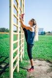 一件蓝色衬衣和绑腿的年轻人适合的妇女训练户外在日落的 做舒展在肋木的健身妇女 健康lif 免版税库存图片