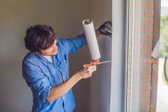 一件蓝色衬衣的人做窗口设施 库存图片