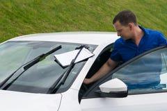 一件蓝色衬衣的人在度假乘聘用的一辆白色汽车 免版税图库摄影