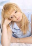 一件蓝色衬衣的哀伤的新白肤金发的妇女 库存图片