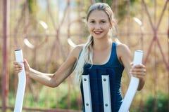 一件蓝色衬衣的少妇使用在外面公园适合和运动的妇女训练的室外健身房设备 库存图片