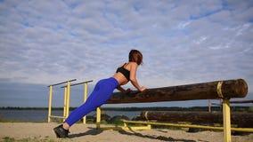一件蓝色衬衣的美丽的女孩在蓝天和蓝色河背景执行从树被按 体育运动 股票录像