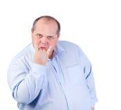 一件蓝色衬衣的肥胖人,显示淫秽姿态 图库摄影