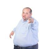 一件蓝色衬衣的肥胖人,点手指 免版税库存照片