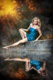 一件蓝色长的礼服的少妇在日落在森林里 库存图片