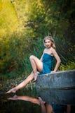 一件蓝色长的礼服的少妇在日落在森林里 图库摄影