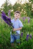 一件蓝色T恤杉的可爱的男孩有羽扇豆花束的在草甸 免版税图库摄影